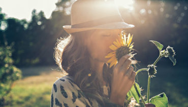 woman smelling sunflower