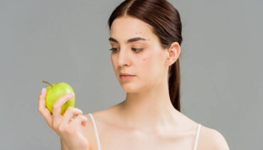 woman with acne looking at an apple she's holding